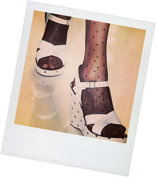 Polaroid of a woman's legs, she's wearing a custom pair of platform sandals on a fashion runway.